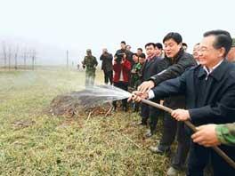 2月7日,温家宝在河南省禹州市鸿畅镇东高村的麦田里,拿起塑料水管为麦田浇水。