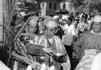 1960年4月,周恩来访问缅甸时,身着缅甸民族服装,手持银碗,同缅甸人民欢庆泼水节。