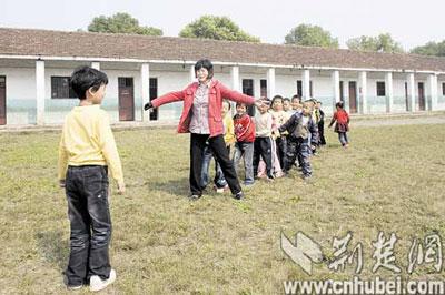 虽然右臂装着义肢,十分不便,但与孩子们玩起课间游戏时仍乐此不疲。