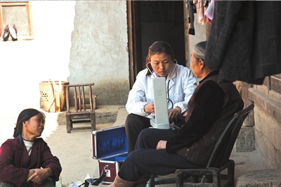田蕊在给村里的老人量血压。红基会供图