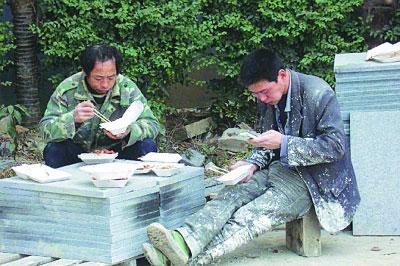 民工二代穿着满是泥浆的衣服,吃完饭拿出手机,放松心情。 网友供图