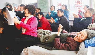 19日,武贞贤老人在观看网络义工们表演节目。