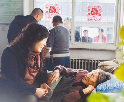 """19日,武贞贤老人和网络义工""""荭草""""(前左)聊天。"""