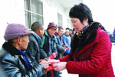 魏小媛向村民派发红包。