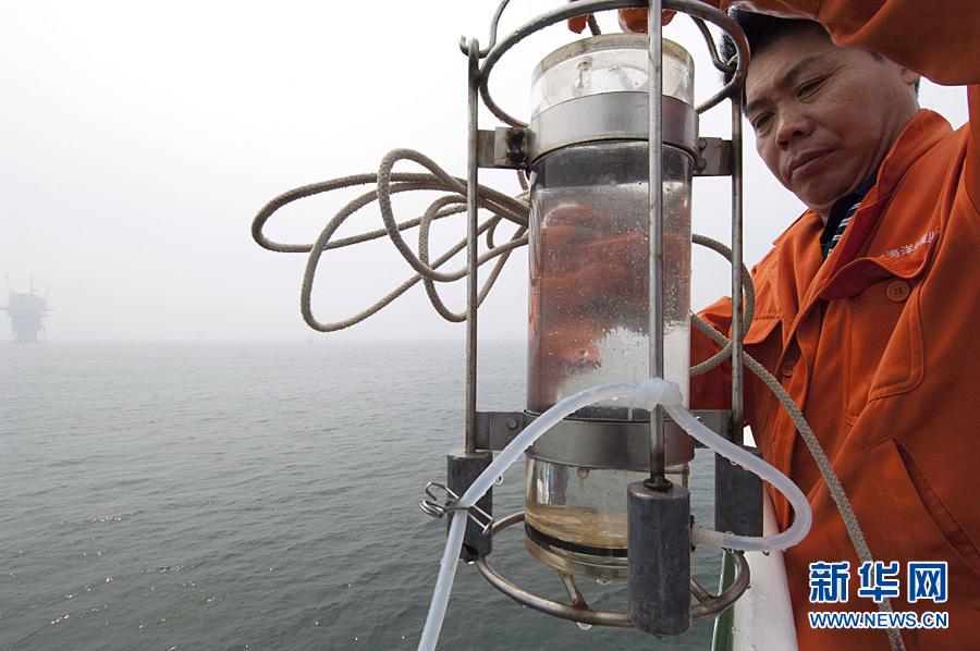 7月15日,国家海洋局北海环境监测中心工作人员对出现赤潮海域采取水样。