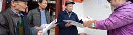刘富祥(右二)在向当地村民发放简报。