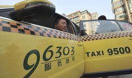 """12月26日,一名电话叫车的乘客乘坐河北唐山一辆印有""""96303服务热线""""字样的出租车。新华社发(郑勇 摄)"""