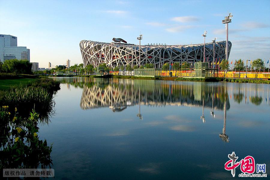 国家体育场是奥林匹克公园的标志性建筑物之一,它位于中心区中轴线东侧、龙形景观水系的西侧。同国家游泳中心、国家体育馆分列于中轴线两侧。中国网图片库 张学胜摄