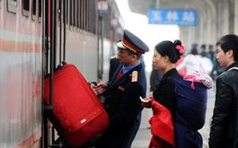 1月25日,在廣西玉林火車站,列車員幫助乘車的旅客拿行李
