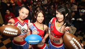 """职业美式足球联盟(NFL)超级杯大赛台湾时间4日上午 7时30分开打,台北市1家运动主题餐厅举办看球派对。店家请来正妹穿上拉拉队服,发送小橄榄球给球迷。(图片来源:台湾""""中央社"""")"""