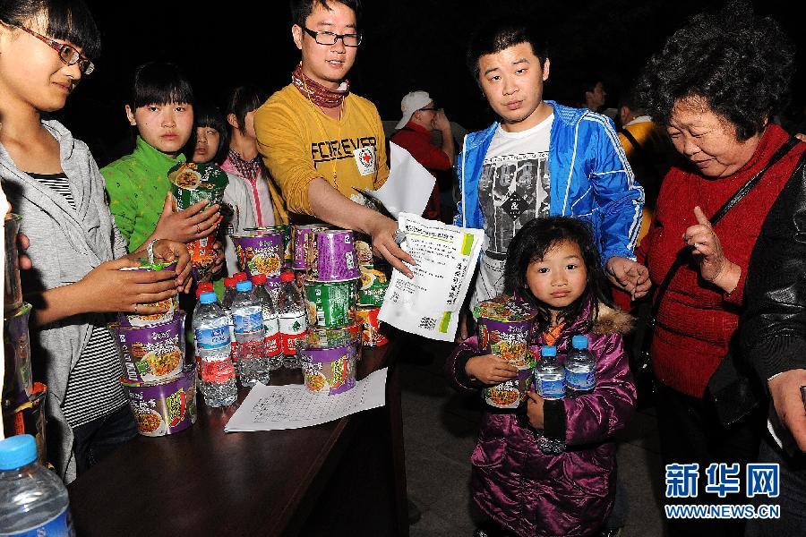 中国 何俊昌/4月21日,中国红十字会工作人员在为受灾群众发放药品、食品...
