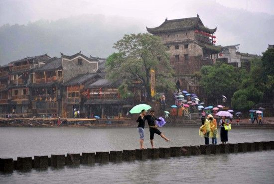 4月29日上午11時23分,幾名遊客冒雨在沱江跳岩上拍照。一場降雨讓許多遊客留在了酒店和客棧裏。