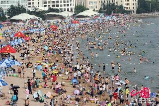 2013年7月7日,人们在青岛第一海水浴场戏水消暑。中国网图片库 黄杰显摄影