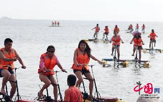 7月7日,人们在青岛第一海水浴场骑水上自行车。中国网图片库 黄杰显摄影