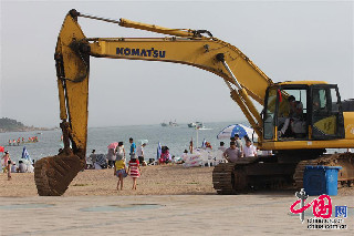 7月7日,人们在干净的青岛第一海水浴场戏水,一台清理浒苔的挖掘机停在旁边。中国网图片库 黄杰显摄影
