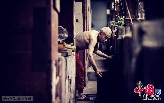 2013年7月14日,青岛。即将动迁的博山路里院,一位老人探身拾取炉上的茶壶。中国网图片库 王海滨摄影