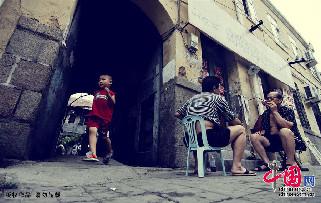 2013年7月14日,青岛。老街上,两位老青岛在石板路上聊天,刚好一名男孩从里院跑出。中国网图片库 王海滨摄影