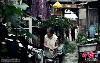 2013年7月14日,青岛。博山路里院,一位大妈在淘米做饭。中国网图片库 王海滨摄影