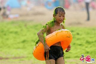 2013年7月18日,青岛,一名男孩身上沾满浒苔。  中国网图片库 王海滨 摄影