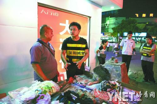 陈润红(左二)给曾经一起摆摊的黄师傅讲解如何合法经营