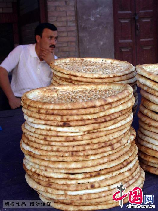"""在维吾尔族眼中,馕就是生命,他们有句名言:""""馕是信仰,无馕遭殃""""。中国网图片库 孙继虎/摄"""