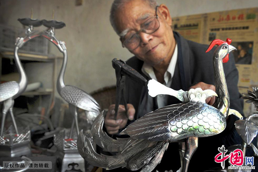 应业根在雕琢一件凤凰锡雕工艺品。中国网图片库 张建成/摄