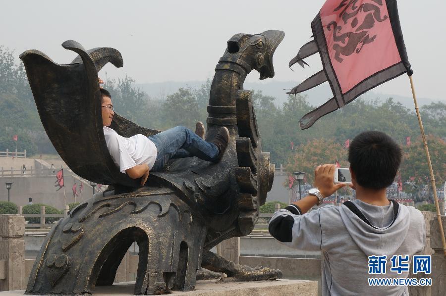 10月1日,在河南省焦作市影视城,一名游客躺在景观雕塑上拍照留影。当日是国庆长假第一天,一些游人在旅游景点随意攀爬、乱刻乱画、乱丢垃圾,成为旅游的不和谐音符。