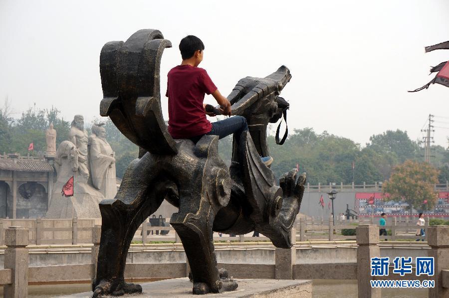 10月1日,在河南省焦作市影视城,一名游客骑在景观雕塑上拍照留影。当日是国庆长假第一天,一些游人在旅游景点随意攀爬、乱刻乱画、乱丢垃圾,成为旅游的不和谐音符。