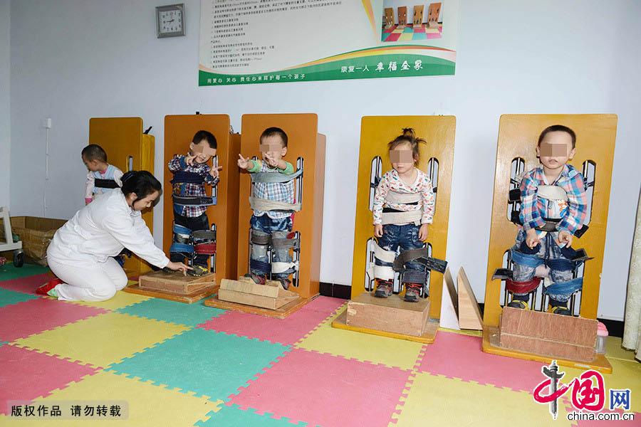 在康复室里,几名脑瘫儿童正在接受站立姿训练。中国网图片库 周会/摄