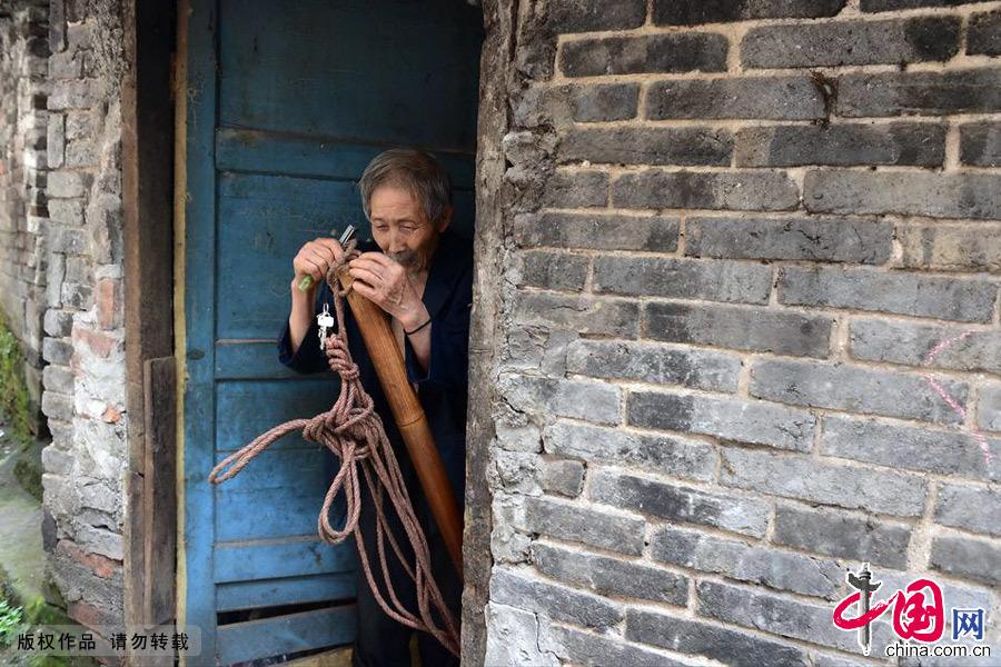 甘在思在租住的房舍门口往棒棒上套绳索,准备出发揽活干。中国网图片库 周会/摄