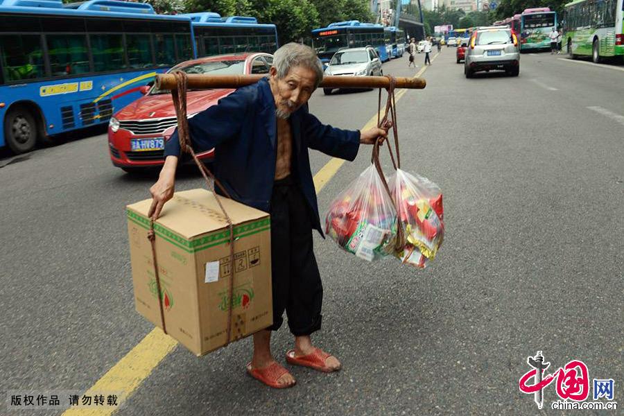 甘在思挑着货物步履蹒跚地穿梭于人群和车流中。中国网图片库 周会/摄