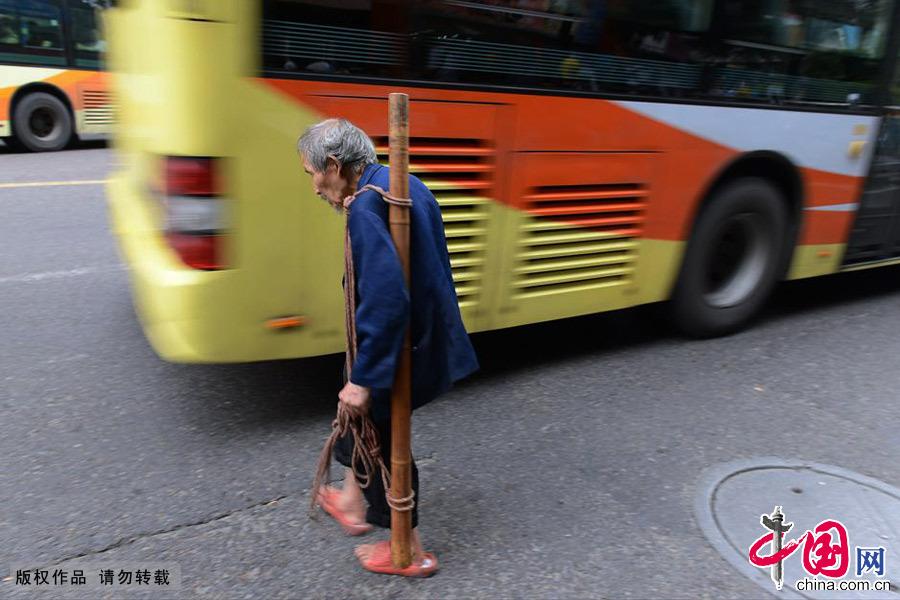 驼着背迈着蹒跚的步履穿梭在车流中,一天要好几个来回。中国网图片库 周会/摄