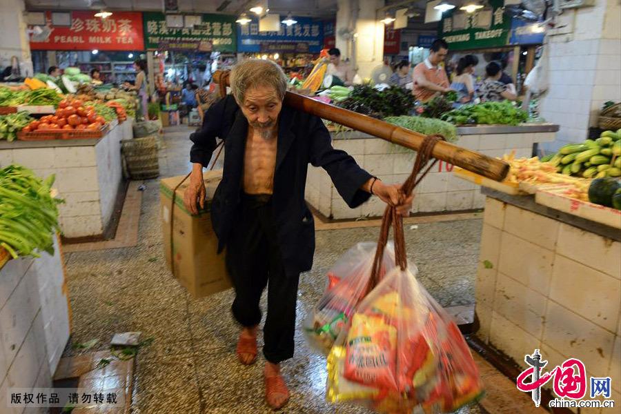 年纪大了行动比别人总是慢了许多,但是周围的人们都很照顾他。会刻意给些轻便的货物,还有的会塞给他面包和水。中国网图片库 周会/摄
