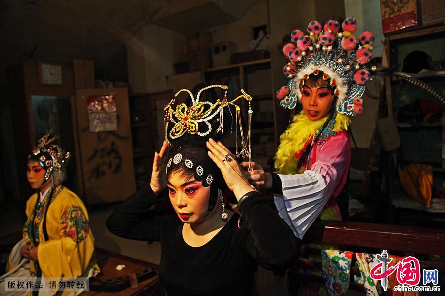 表演前,演员们互相整理戏服。从开张到现在,缘于对川剧的热爱,龙潭剧社的演员们已经整整坚守了11年。中国网图片库 刘传福/摄