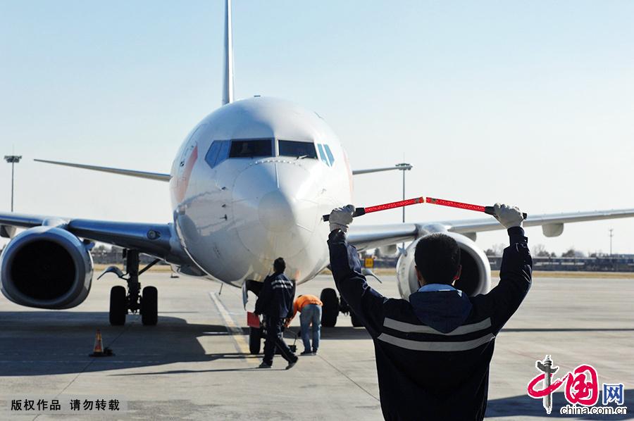 在呼和浩特白塔国际机场,一名引导员正在引导飞机进入指定位置.