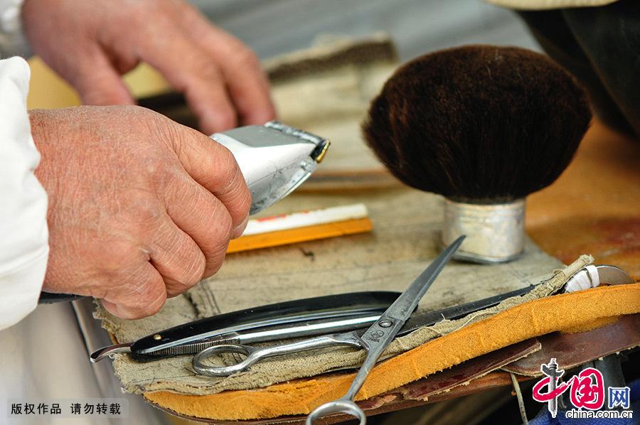 简单而又传统的工具,被风霜侵袭的手,还有不曾忘却的理发技艺,这一街景,曾留在很多老一辈人的记忆深处。中国网图片库 王海滨/摄