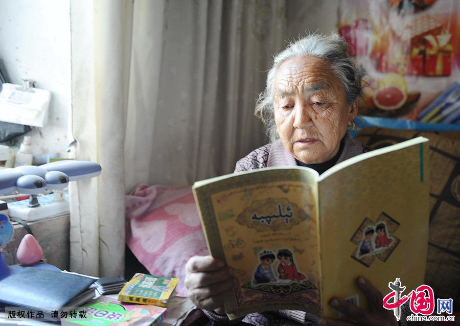 潘玉莲老人认真研读标准教材。通晓汉语、维语、俄语、藏语的她发挥自己的优势,为孩子们辅导功课。中国网图片库 邹建奇/摄