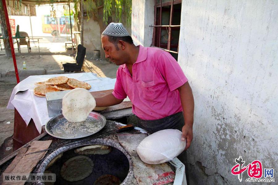 庫爾班從十三歲就開始烤馕,已經烤馕二十多年。為了自己心中的夢想一家人從喀什葉城縣來到哈密。中國網圖片庫 孫繼虎/攝