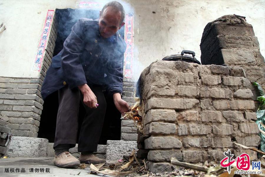 11月13日,河南平顶山市宝丰县石桥镇兴隆村村民党员张山正在烧火做饭。中国网图片库 何五昌摄