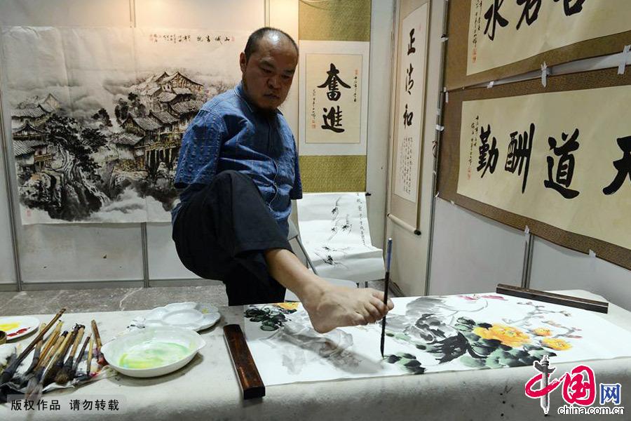2013年11月7日,无臂残疾人黄国富用脚执笔作画。中国网图片库 周会/摄