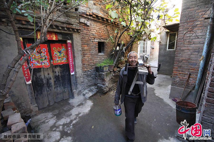 """""""磨剪子嘞戧菜刀......""""在開封市大南門的一個小衚同裏,65歲的老崔肩上扛著板凳走在衚同裏大聲吆喝著。 中國網圖片庫 楊正華/攝"""