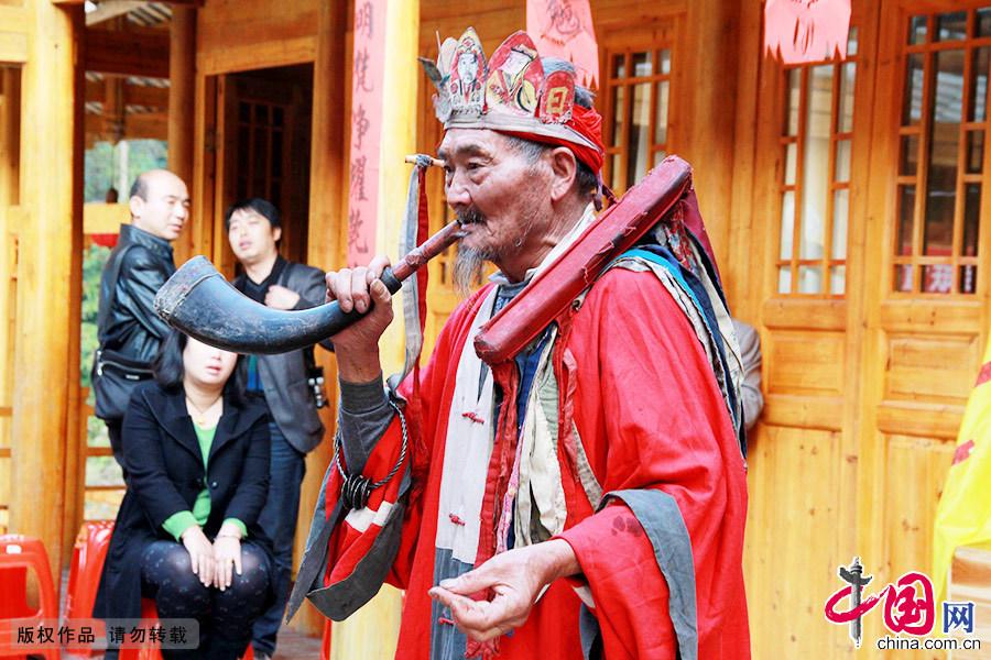 儺戲傳承人楊勝淮穿著法衣吹著牛角正在表演儺堂戲。中國網圖片庫 陳曉嵐/攝