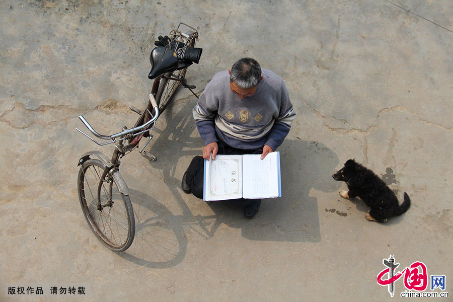 """在庭院裏,""""鄖縣袁隆平""""徐自強查看自己近年來收集的紅薯研究資料和獲得的證書,破舊的自行車是他忠實的夥伴。 中國網圖片庫 曹忠宏/攝"""