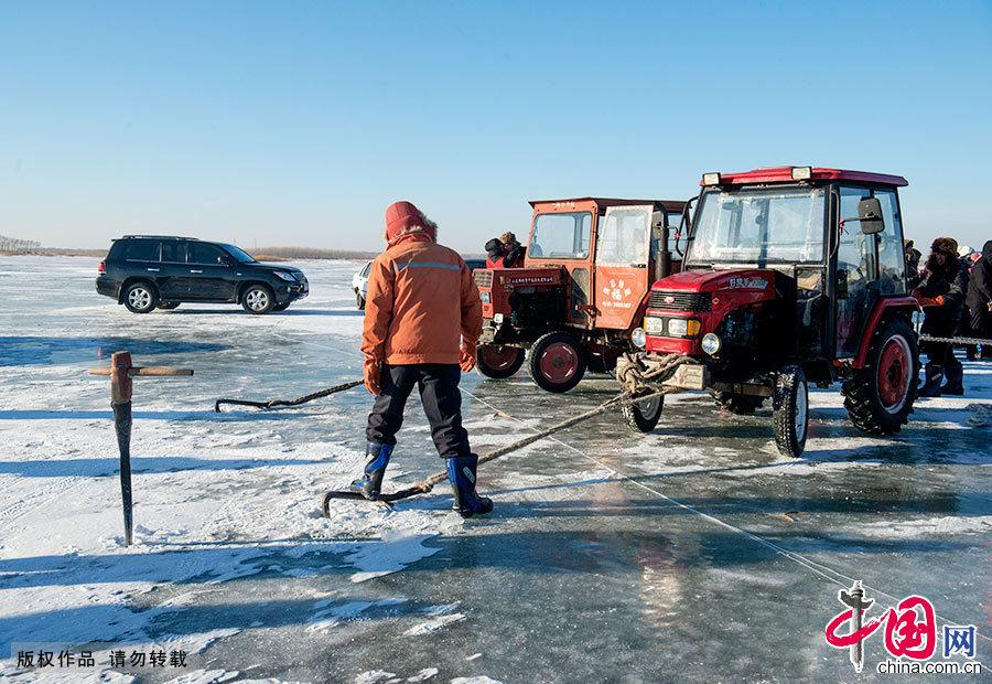 工人们在冰上凿好冰洞后下网,再由拖拉机上的绞盘把渔网拉出。中国网图片库 刘国兴/摄