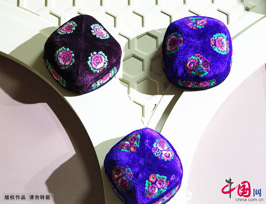 维吾尔族花帽,是维吾尔族服饰中最具特色的部分之一,维吾尔语称'朵帕'。不论天山南北,不论男女老幼,也不分春夏秋冬,维吾尔族人都喜欢戴一顶绣制精美的四棱小花帽。它既是人们日常生活的一种服饰,更是一种令人赏心悦目的工艺品。中国网图片库 孙继虎/摄
