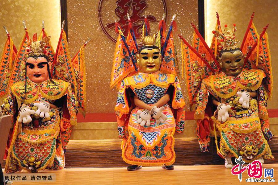 三个扮成哪吒三太子形象的演员,身着传统服饰,背插五色彩旗,在流行音乐伴奏下,跳着可爱逗趣的舞蹈。中国网图片库 孙继虎/摄