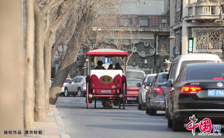 幾名乘客乘坐著馬車遊覽天津五大道風光。在滿大街汽車行駛的都市裏,馬車和馬伕是一道獨特的風景線。中國網圖片庫 澎湃/攝