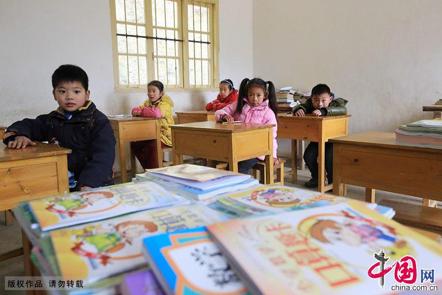 """2月17日,是廣西柳州市融安""""微小學""""——六局村山鎖小學開學的日子。由於學校地處偏遠山區,目前只有6名學生和一位老師。開學第一天,孩子們坐在教室裏等待老師發新書。 中國網圖片庫 譚凱興/攝"""
