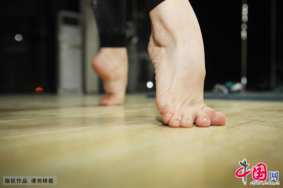 一名队员正在做基本功的训练,因长时间练习,脚趾头都有些变形。 中国网图片库 澎湃/摄