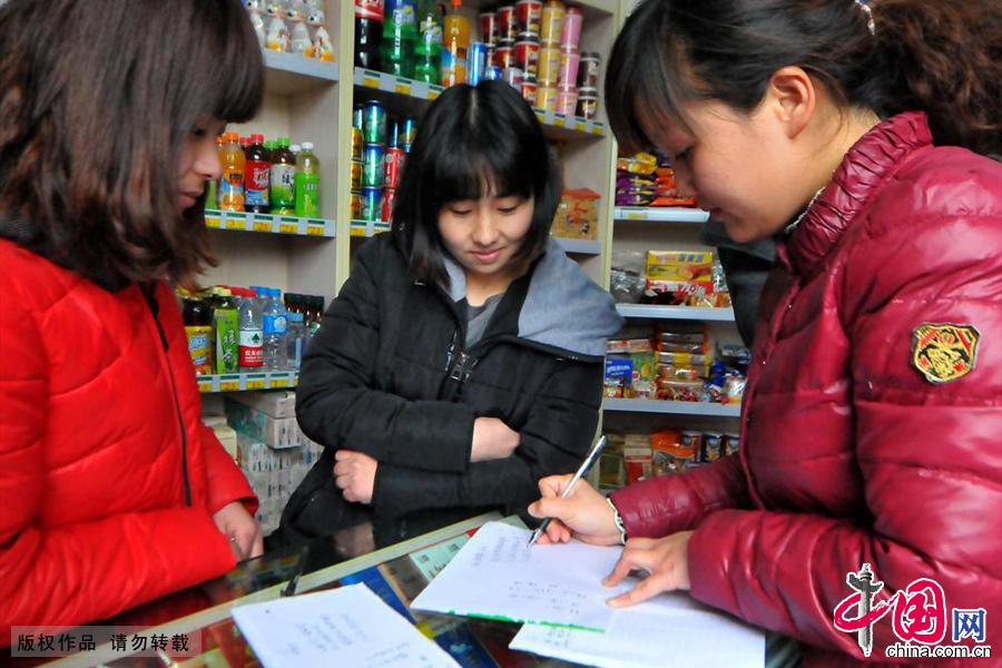 姐姐(中)30歲,妹妹(左)28歲,兩人自幼聾啞。店裏通過手寫的方式與顧客交流,賣出店裏的商品。常來的顧客也似乎習慣了這樣安靜的購物方式。中國網圖片庫 葛傳紅/攝
